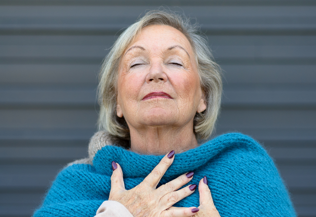 An older woman inhales deeply.