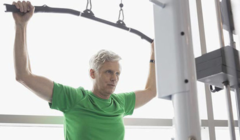 Man uses a lat pulldown machine in a gym.
