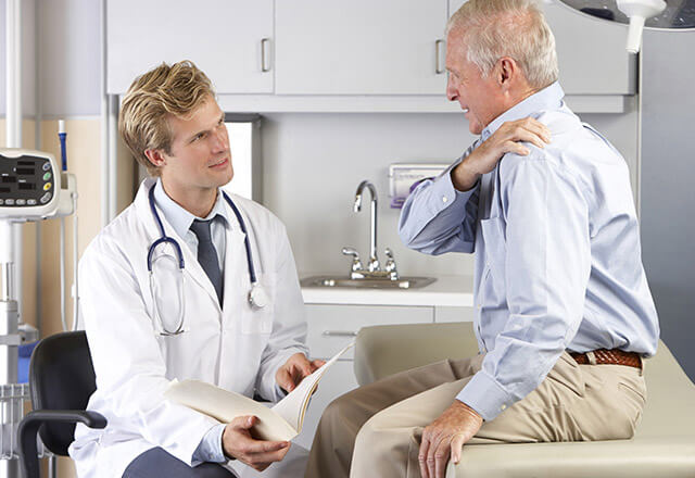 elder patient grabbing shoulder and talking to doctor