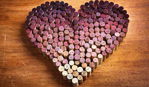 Pink and red wine corks bunched into the shape of a heart.