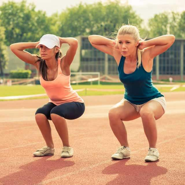 two female athletes doing squats
