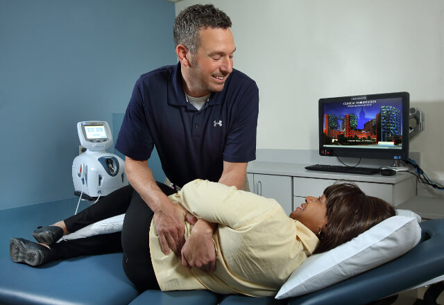 A physical therapist helping patient with back pain.