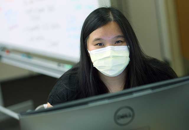 Employee wearing a mask and looking at a computer.