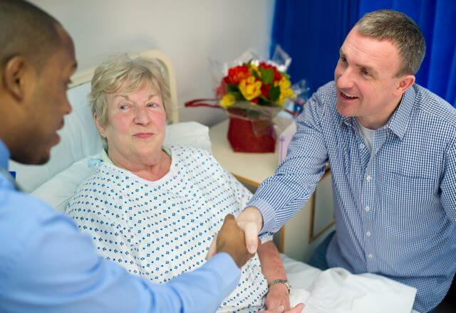 Patient in hospital bed accompanied by visitor and hospital staff member shaking hands