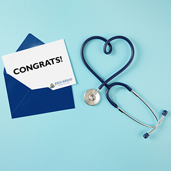 An open envelope with a congratulatory note lays on a blue background next to a stethoscope.