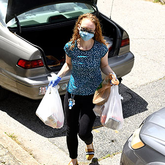 A volunteer carries in groceries from her car.