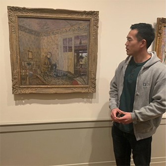 Howard Chang looks at art on display.