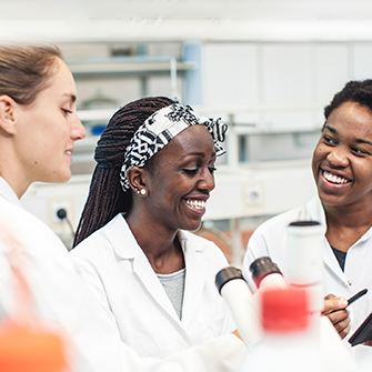 A diverse group of young women work in the lab together.