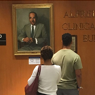 A family looks at the portrait of Vivien Thomas.