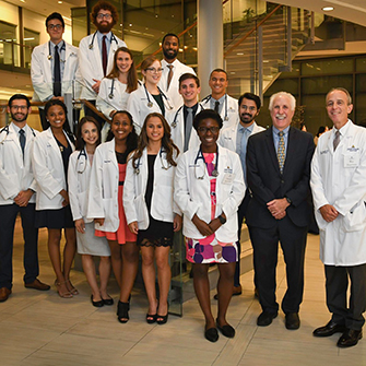 A group of medical students stand in Armstrong lobby with Dean Rothman and Dr. Ziegelstein.