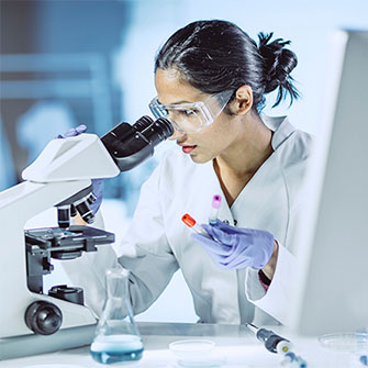 A young female scientist looks into a microscope.