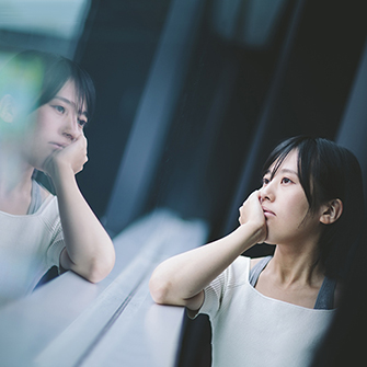 a woman looks out a window with sad expression