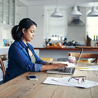 A young woman works on her laptop at the kitchen table.