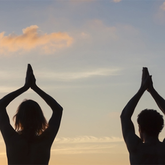 Two people in silhouette perform yoga poses outdoors.