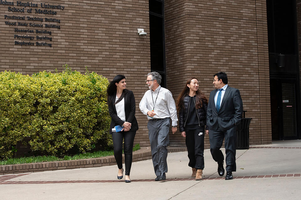 Dr. Gregg Semenza with students outside the Wood Basic Science Building.