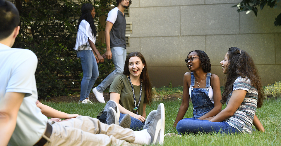 Graduate students sit outside in the grass.