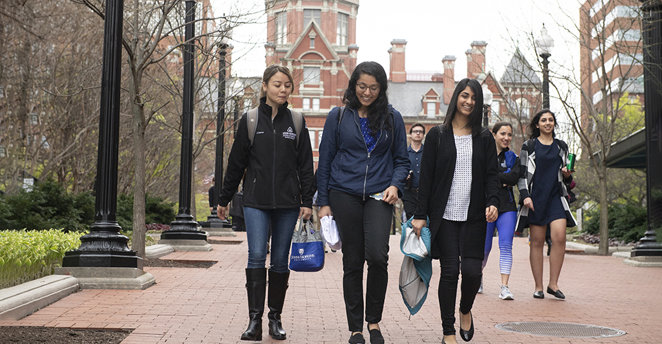 Students walk on the East Baltimore campus, with the Dome in the background.