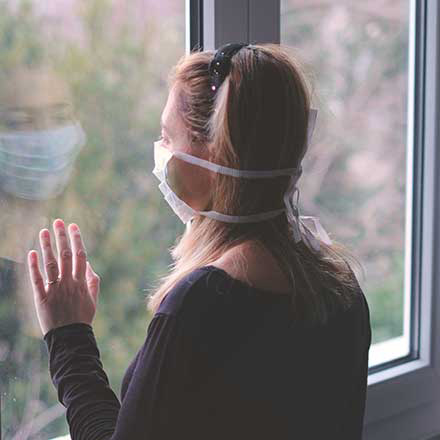 masked woman looking out window