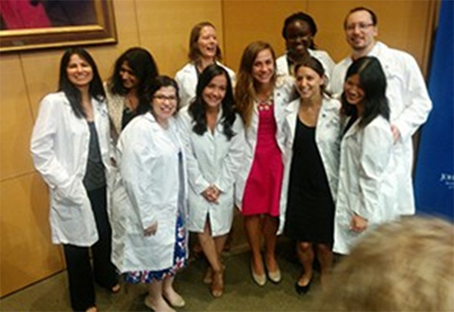 Graduate students pose together happily after receiving their white coats.