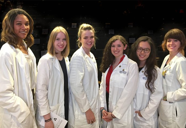 A group of female graduate students stand together with their white coats.