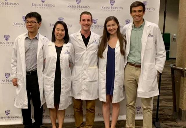 A group of graduate students pose together in their new white coats.