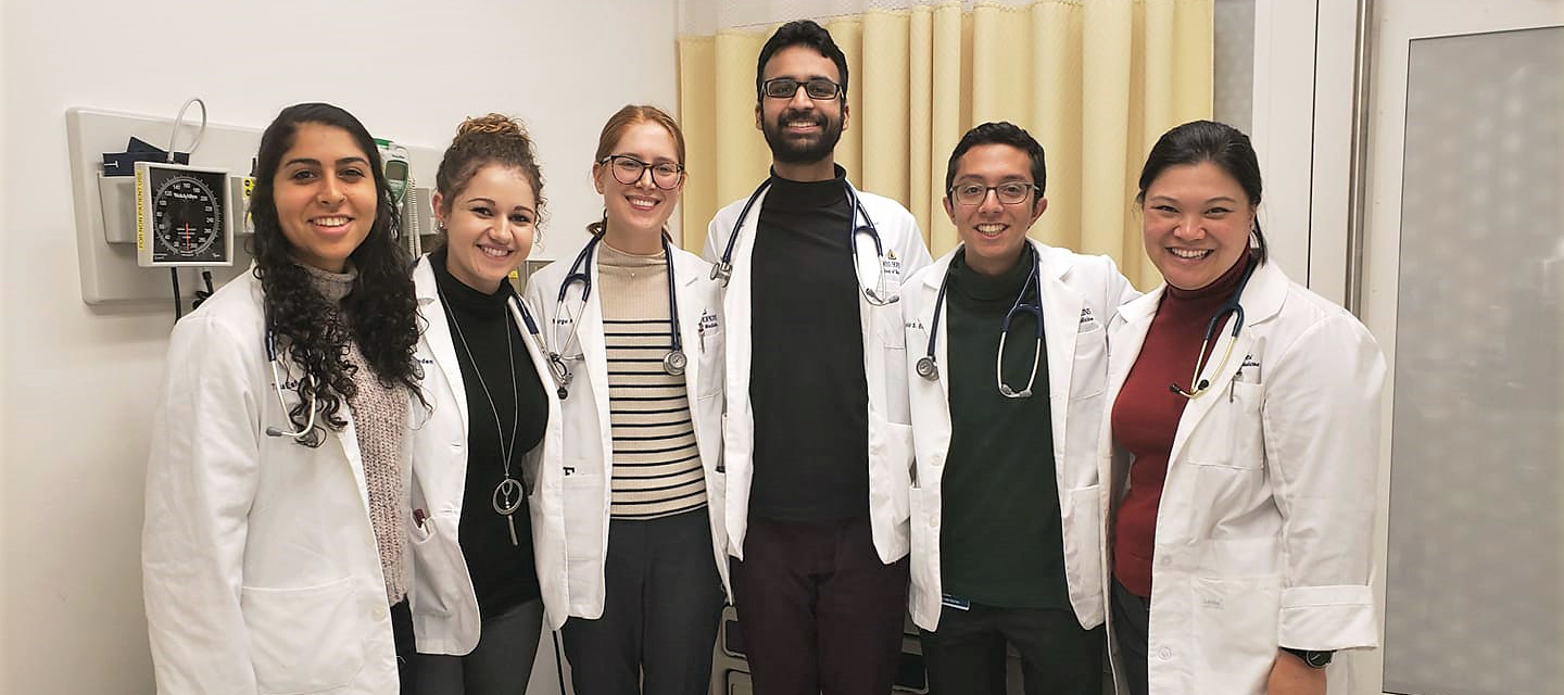A group of medical students stand together wearing white coats and stethoscopes.