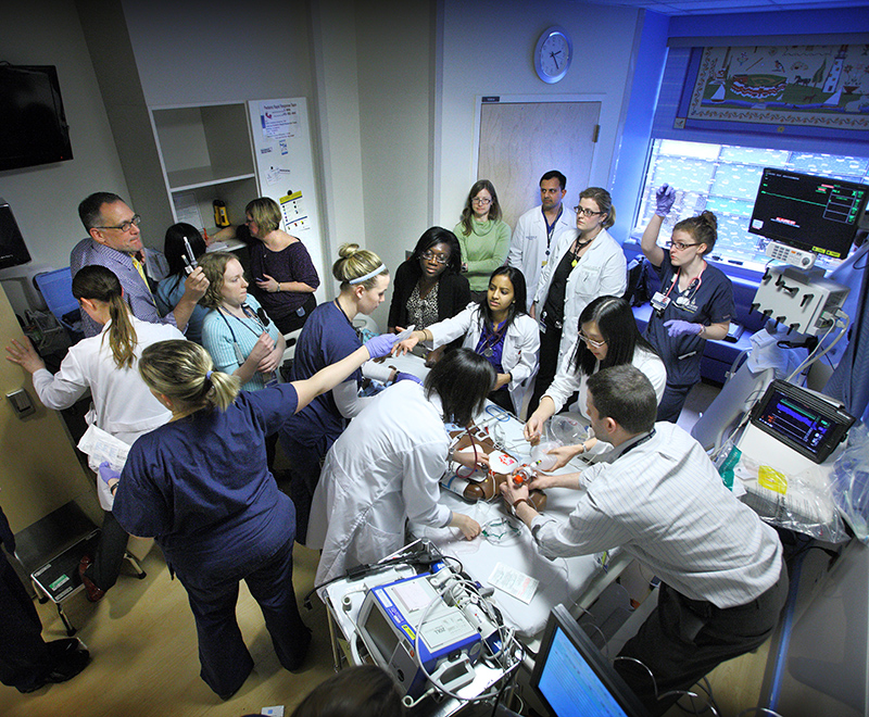 a group of doctors around a hospital bed.