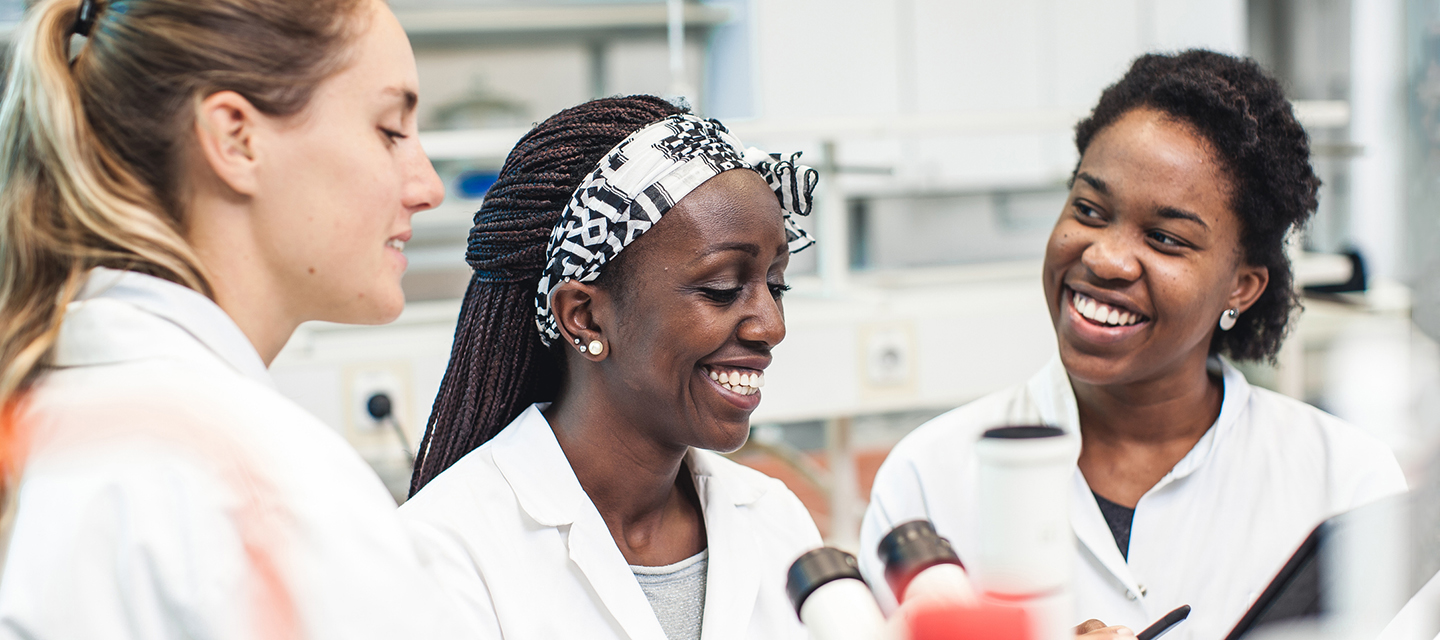 A diverse trio of female students smile together in the lab.