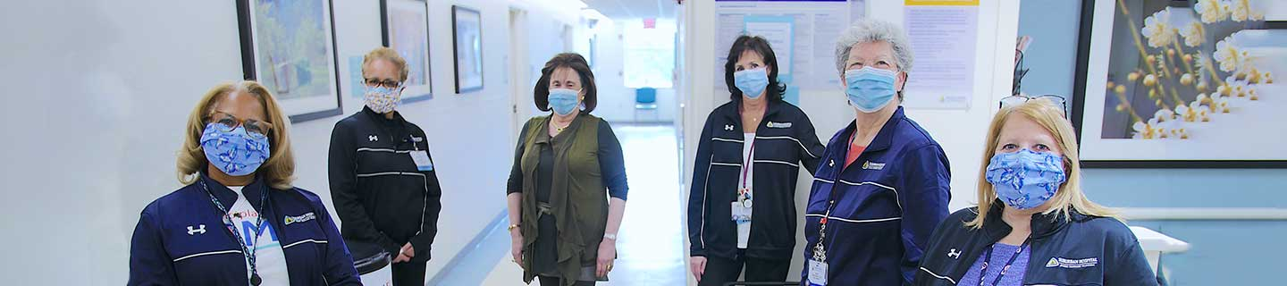 Employees in the hospital hallways wearing masks.