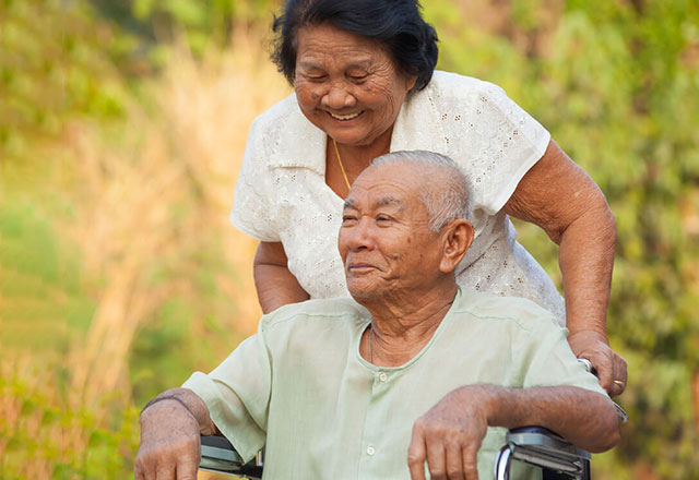 an older woman pushing her husband in a wheelchair