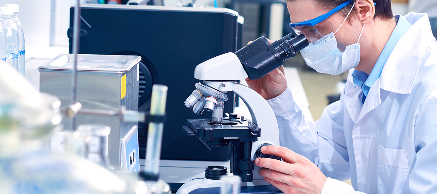 researcher using microscope in lab