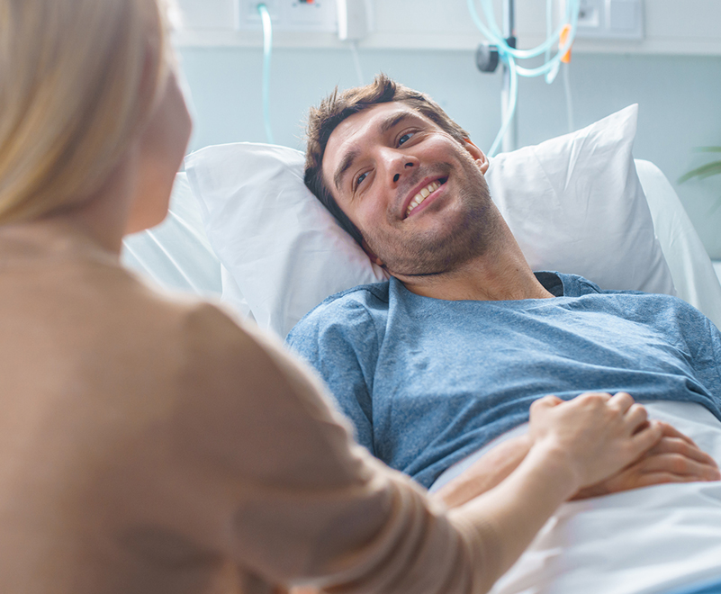 man smiling in hospital bed at loved one