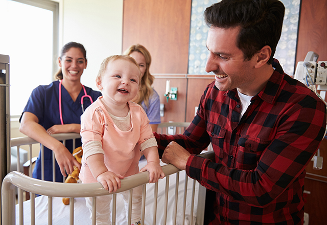 johns hopkins surgery - toddler in crib smiling at father in hospital