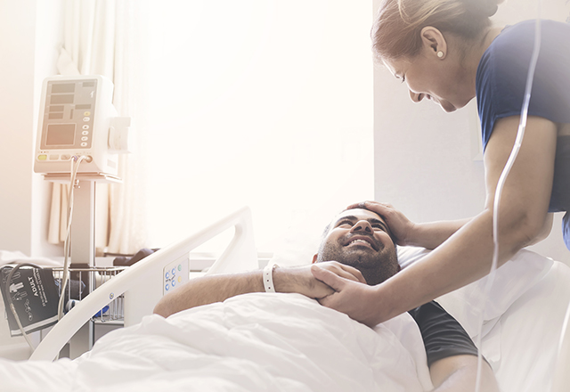 johns hopkins surgery - man in hospital bed being comforted by nurse