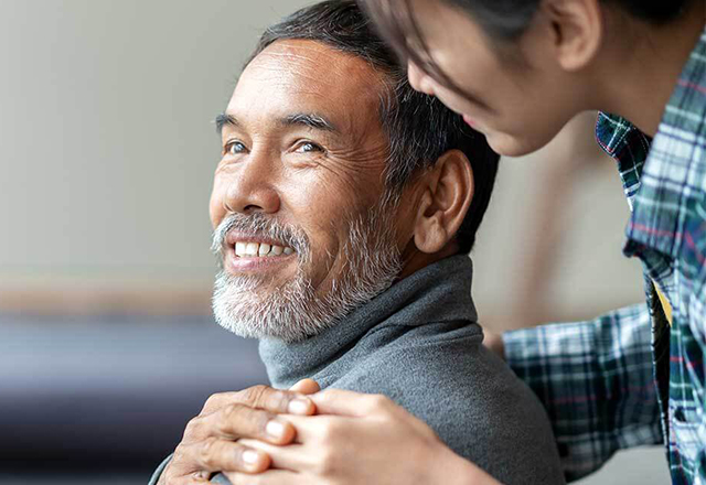johns hopkins surgery - mature man in wheelchair smiling at loved one