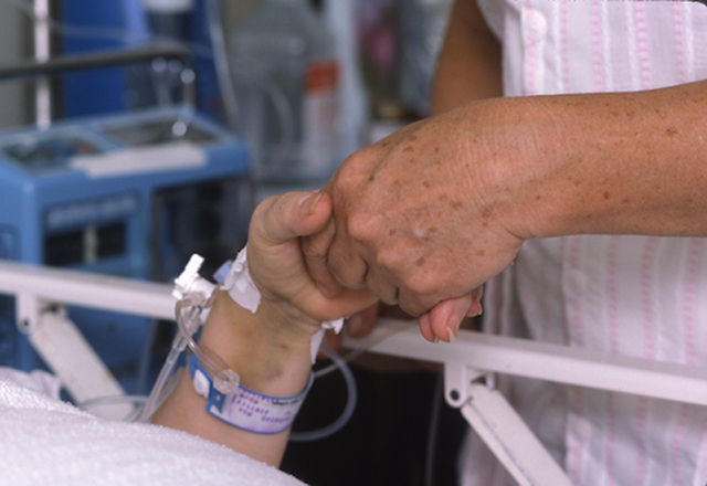 holding hands by hospital bed