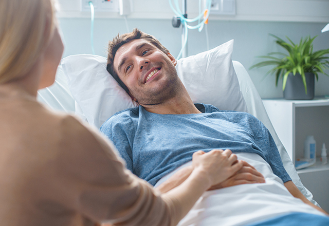 male patient in bed smiling at loved one