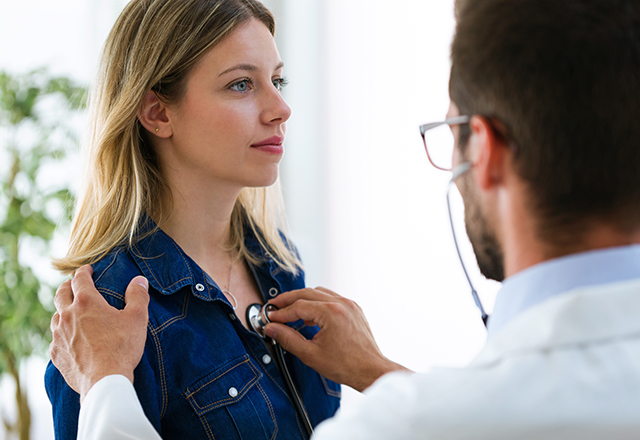 doctor listening to young woman's chest
