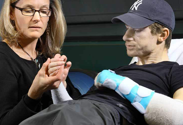 woman examines arm of transplant recipient