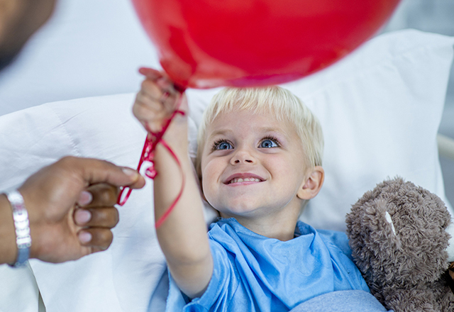 boy in hospital bed holding red balloon