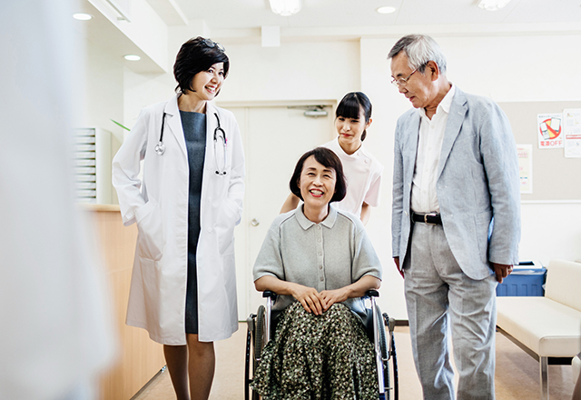 transplant patient information - asian woman in wheelchair being released from hospital