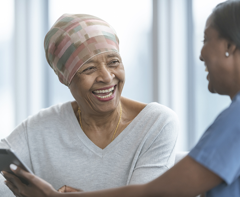 mature woman with cancer laughing with nurse