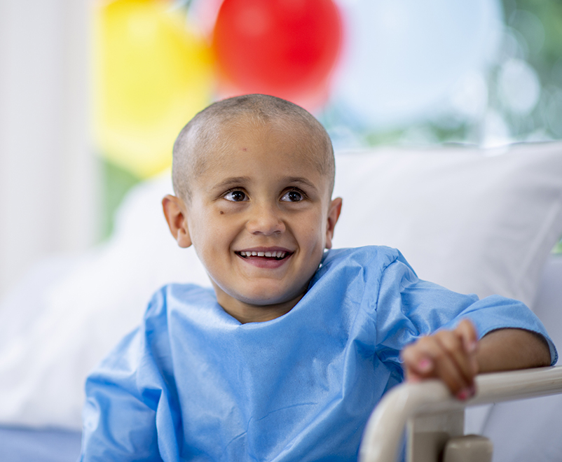 boy with cancer smiling in hospital bed