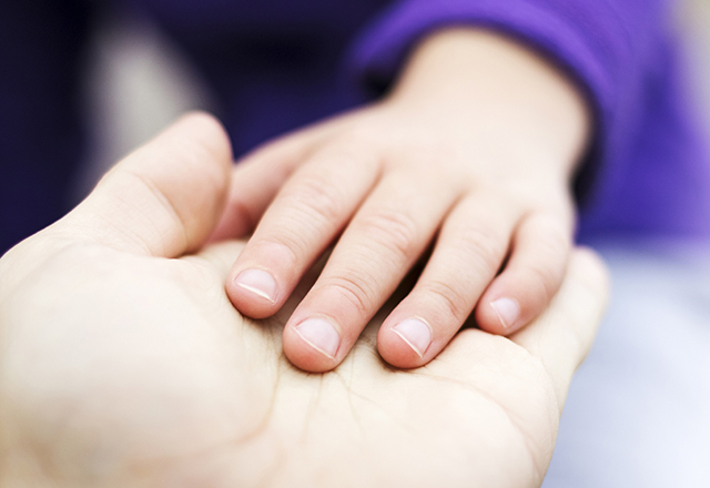 child placing hand over adult hand