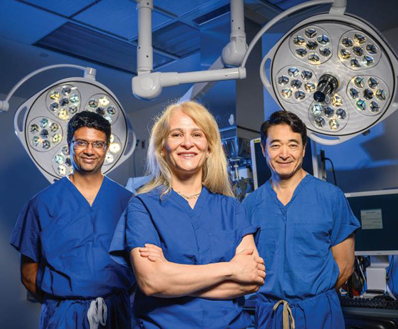 Dr. Ramulu, Dr. Akpek and Dr. Handa standing in an operating room