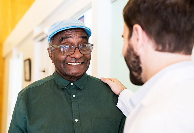 man with glasses smiling at doctor
