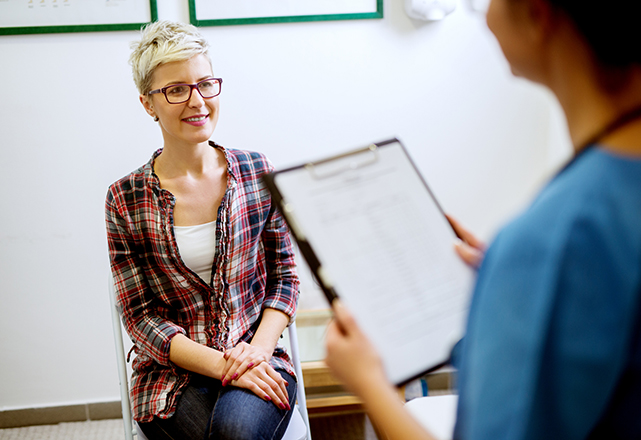 woman wearing glasses sitting in exam room