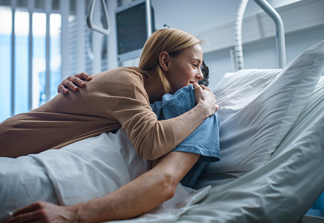 reconstructive transplant - woman hugging loved one in hospital bed