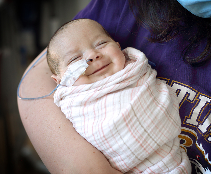 smiling baby in mothers arms