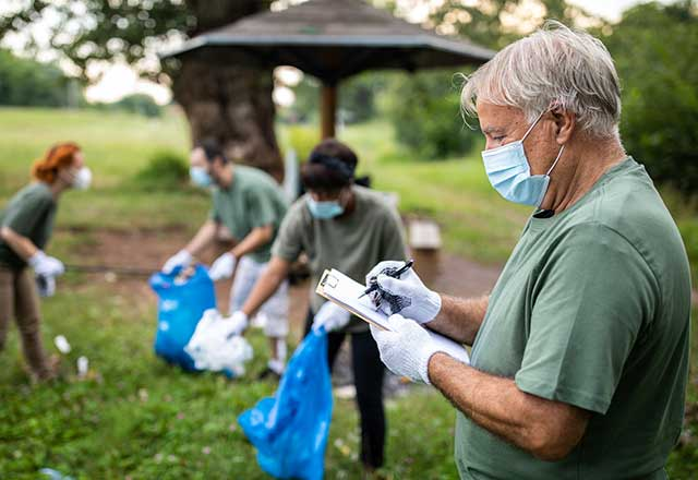 Masked volunteers cleaning up a park.